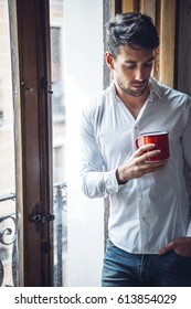 Young sad male in casual outfit holding red mug and standing near window in rain.