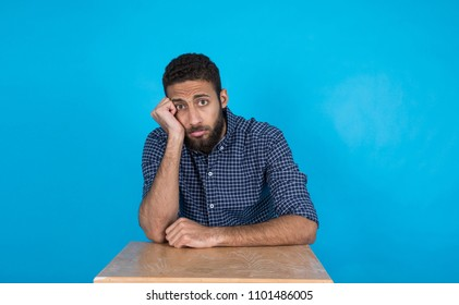 Young sad man sitting on a wooden desk with frowning face emotion hand on cheek on a blue background.