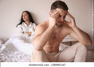 Young sad man sitting on bed after quarrel with wife