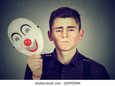 Young sad man taking off happy clown mask isolated on gray wall background. Human emotions. Split personality concept
