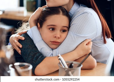 Young sad mother hugs little upset daughter sitting in lawyer's office for divorce. Two parents fighting over child in divorce concept.