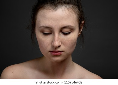 young sad pensive woman with a freckles closeup portrait on black background