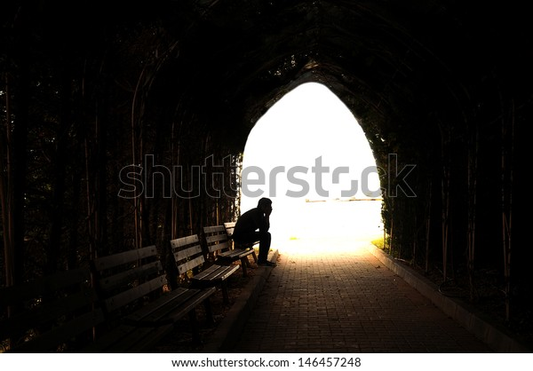 young sad sitting in the dark tunnel
