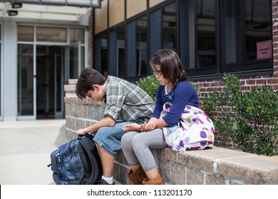 Young sad teenagers in front of a school building