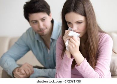 Young sad woman crying, wiping tears off her face, loving boyfriend consoling troubled young girlfriend, compassionate guy supporting weeping lady, comfort and support, catching cold and sneezing