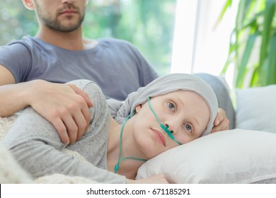 Young sad woman resting with oxygen nasal cannula on