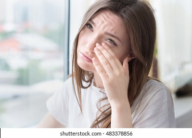Young sad woman sits alone front of the window. Crying girl. Allergy, illness, depression, stress concept.