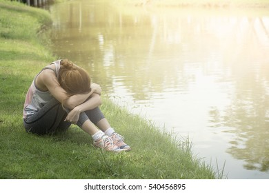 Young sad woman sits alone front  the lake. Crying girl. Allergy, illness, depression, stress concept.