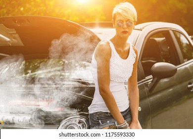 Young sad woman standing near the road by the broken car in the middle of nowhere. Smoke coming out from overheat engine. Waiting car tow service.