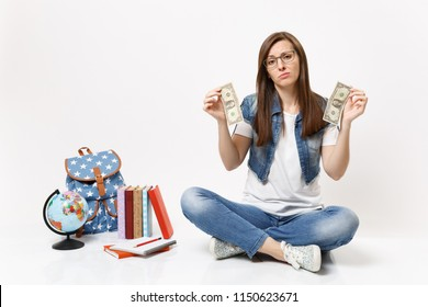 Young sad woman student in glasses holding dollar bills have problem with money sitting near globe, backpack, school books isolated on white background. Education in high school university college