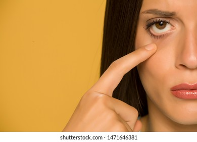 Young sad woman touching her  low eyelids on yellow background