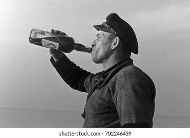 Young sailor drinking a bottle of wine