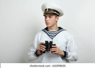 Young sailor holds binoculars in hands on a white background