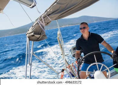 Young sailor skipper manages sailing vessel during regatta race in the open sea.