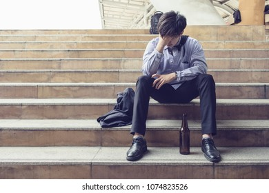 Young salaryman sitting stress and depressed with bottle alcohol from unemployment