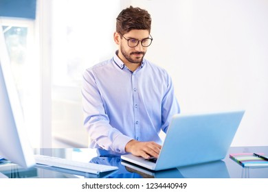 Young sales man typing on his notebook while sitting in the office and working on new project.
