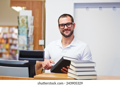 Young salesman at the checkout in a bookstore