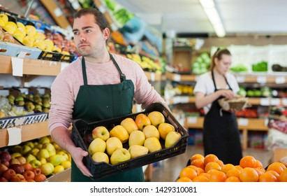 Young salesman holding box of fresh apples during work on the supermarket