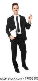 Young salesman holding car key on white background