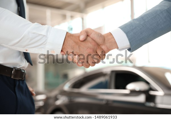 Junge Verkäufer, die im modernen Autohandel die Hände des Kunden schütteln, Nahaufnahme