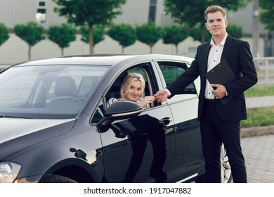 A young salesman shows a new car to customers. Happy woman buy a new car. The young woman is behind the wheel, the seller gives her the keys