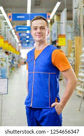 Young salesman standing at construction super store. Portrait of attractive confident working man in uniform on his workplace in building store.