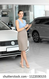 Young saleswoman with clipboard in car dealership
