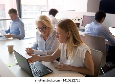 Young saleswoman manager mentor advisor consulting old female client or new employee pointing at laptop showing business presentation teaching instructing at meeting in modern corporate shared office