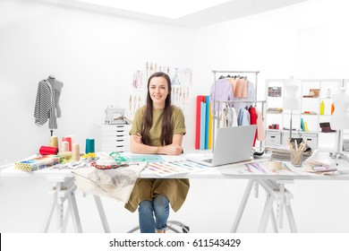 young saleswoman sitting at the desk in front of her laptop in the showroom