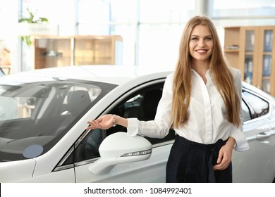 Young saleswoman standing near new car in salon