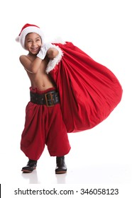 Young Santa.  Adorable mixed race boy pretending to be Santa Claus.  Isolated on white.