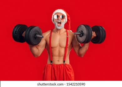 Young Santa Claus bare muscular upper body wearing hat and sunglasses standing isolated on red background christmas concept holding dumbbells exercise shouting cheerful