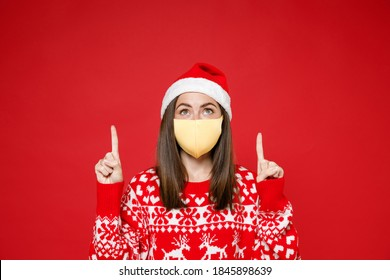 Young Santa woman in sweater Christmas hat face mask to safe from coronavirus virus covid-19 pointing index fingers up isolated on red background. Happy New Year celebration merry holiday concept