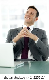 Young satisfied businessman at workplace