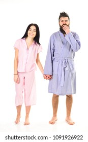 Young satisfied couple in love cuddling gently in pajamas at home. Couple in love holds hands, isolated on white background. Relationship and weekend goals