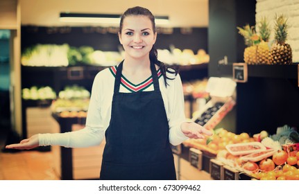 Young satisfied  shopping assistant demonstrating assortment of grocery shop