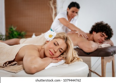 Young satisfied woman and man enjoying at beauty salon. Female therapist massaging young man's back, and woman lying down and waiting for relaxing  massage.