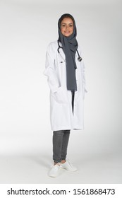 Young Saudi female doctor wearing doctor uniform and Hijab and Stethoscope in various positions, expresseions and hand gestures on white isolated background.