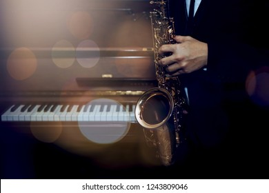 A young saxophone player holding alto saxophone over piano key in the night with light effected and Bokeh from above, music background