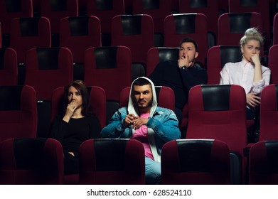 Young scared adults watching horror movie