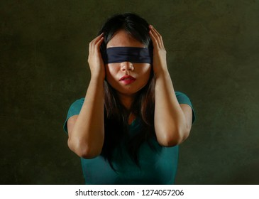 young scared and blindfolded Asian Chinese teenager girl lost and confused playing dangerous internet viral challenge isolated on dark background under edgy and dramatic studio light