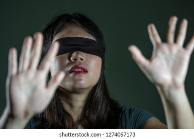 young scared and blindfolded Asian Korean teenager girl lost and confused playing dangerous internet viral challenge isolated on dark background under edgy and dramatic studio light