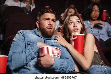 Young scared couple watching a horror movie while sitting at the cinema with popcorn