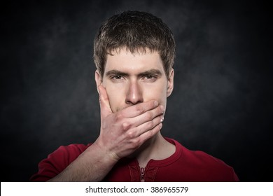Young scared man hand covering mouth over dark background.