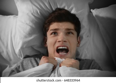 Young scared man lying in bed at home