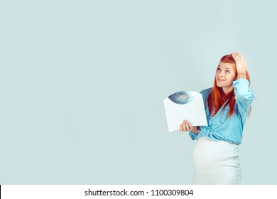 Young scared pregnant woman having overweight and holding weight scales looking up in worries isolated on blue. I got some extra kilos during pregnancy concept