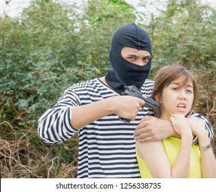 Young scared woman hostage victim locked by threatening robber in day time. Gangster criminal cover face with black mask pointing gun at hostage. Criminal, kidnap, terrorist, property & life Insurance