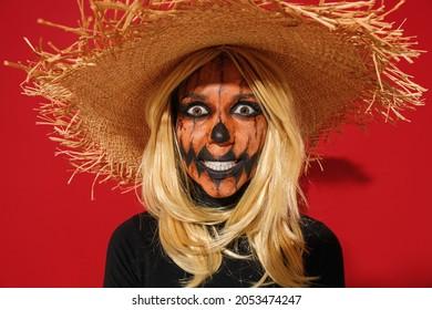 Young scary caucasian woman with Halloween makeup mask wears straw hat black scarecrow costume look camera say booo isolated on plain red background studio portrait. Celebration holiday party concept