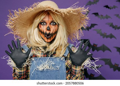Young scary creepy woman 20s with Halloween makeup mask in straw hat scarecrow costume spread hands say booo isolated on plain dark purple background studio portrait Celebration holiday party concept