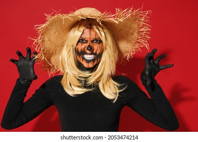 Young scary woman with Halloween makeup mask wearing straw hat black scarecrow costume threatening saying booo isolated on plain red color background studio portrait. Celebration holiday party concept